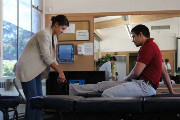 Student intern learning chiropractic looking at patients leg